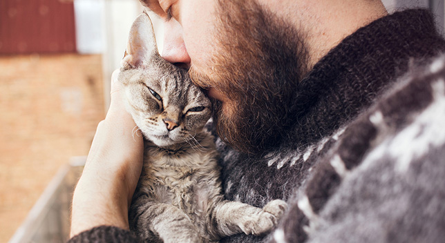 A man cuddles and kisses his cat.