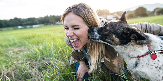 Woman laughs as her dog kisses her.